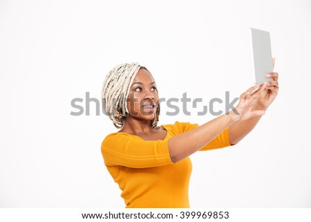 Attractive cheerful young african american woman taking selfie with tablet over white background - stock photo