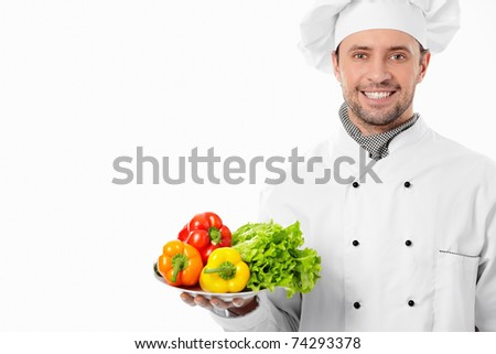 Attractive chef with a plate with vegetables on white background - stock photo