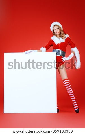 Attractive Christmas girl posing with a white billboard. Copy space. Red background. - stock photo