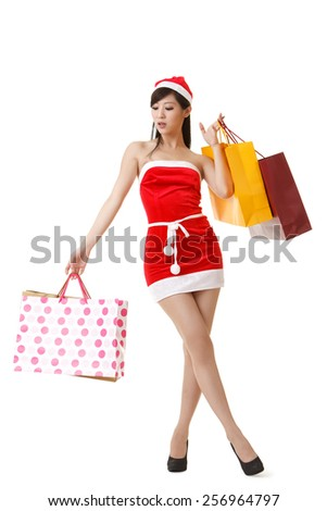 Attractive Christmas lady holding shopping bags, full length portrait isolated on white background. - stock photo