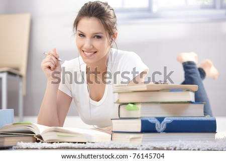 Attractive college girl learning at home on floor, listening to music, smiling.? - stock photo