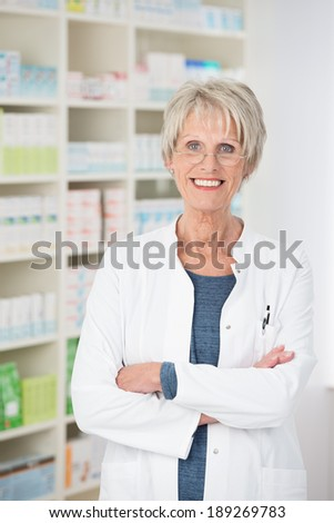 Attractive confident senior pharmacist standing with her arms folded giving the camera a beautiful friendly smile, stocked shelves behind her - stock photo