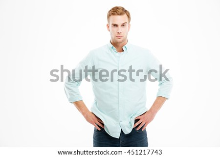 Attractive confident young businessman standing with hands on hips over white background - stock photo