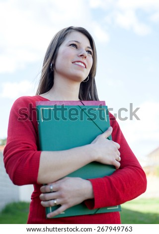 Attractive cool college girl outside with a green folder - stock photo
