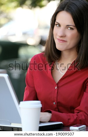 Attractive corporate, business woman working on her laptop with a cup of tea outdoors, in a city street - stock photo