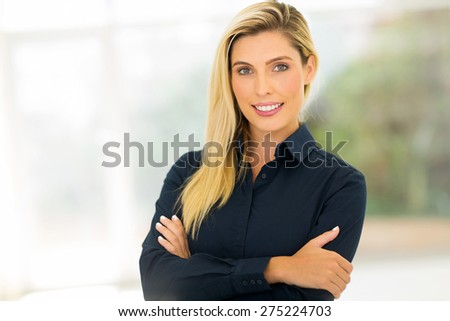 attractive corporate worker standing in modern office - stock photo