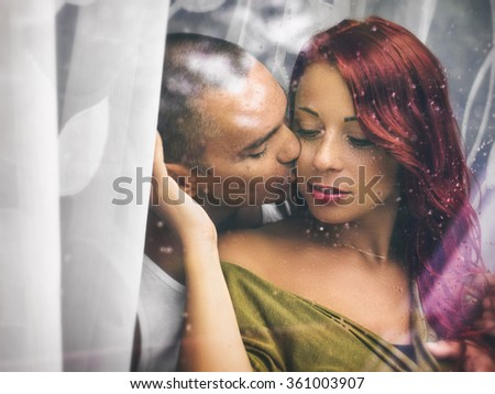 Attractive couple behind a window with water drops, in a rainy day. With custom white balance and color filters - stock photo