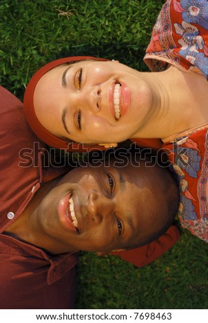 Attractive couple enjoying a summer day together on the grass - stock photo