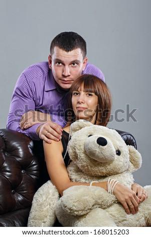 Attractive couple guy, a girl and a teddy bear - stock photo