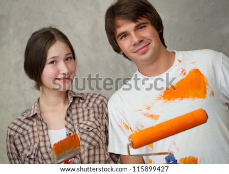 Attractive couple holding brushes - stock photo
