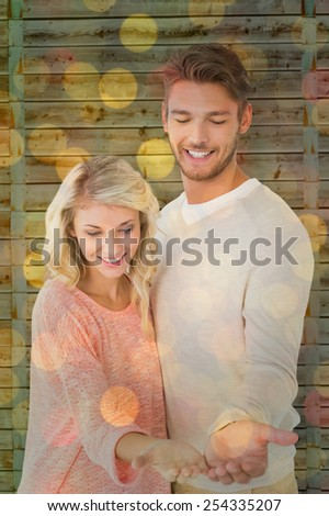 Attractive couple holding their hands out against close up of christmas lights - stock photo