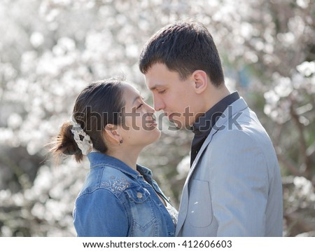 Attractive couple in blossoming park. Asian girl and european guy standing face to face on background of blossoming almond trees - stock photo