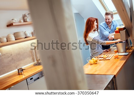 Attractive couple in kitchen preparing meals together - stock photo