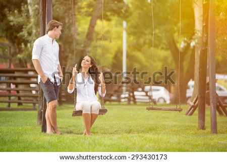 Attractive couple in park on swing, girl sitting on swing man standing next her  - stock photo