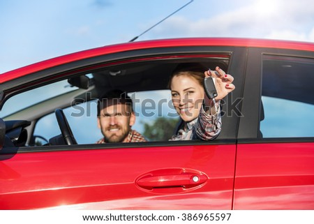 Attractive couple in the red car with the keys of the car at sunset. Concept of travel, rent car or buying car.  - stock photo