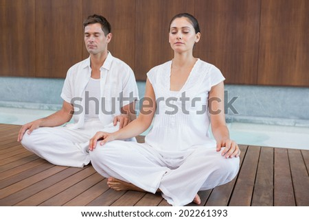 Attractive couple in white sitting in lotus pose in health spa - stock photo