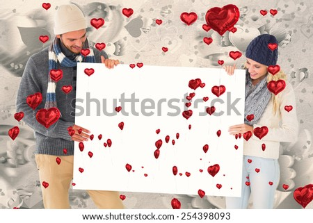 Attractive couple in winter fashion showing poster against grey valentines heart pattern - stock photo