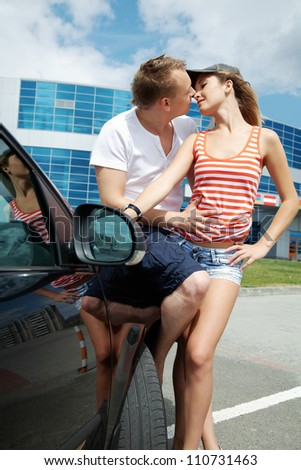 Attractive couple kissing each other near the car outdoor - stock photo