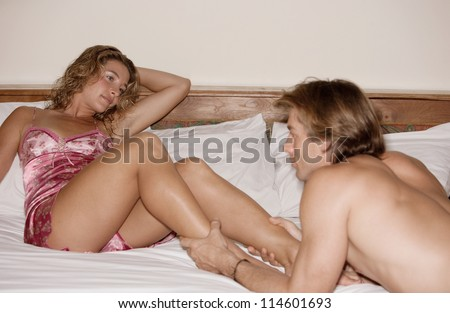 Attractive couple of lovers in bed being intimate with each other. - stock photo