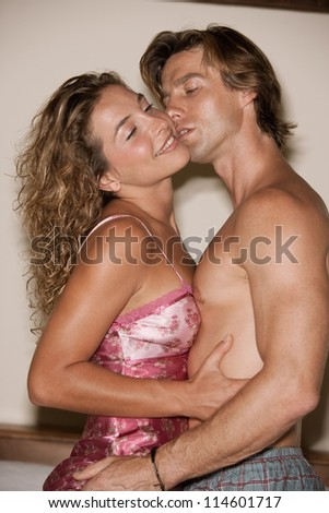 Attractive couple of lovers in bed being intimate with each other and kissing. - stock photo