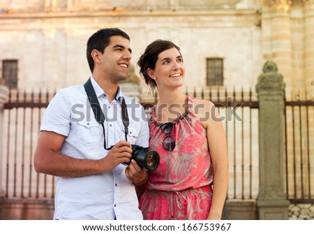 Attractive couple of tourists visiting the city and taking pictures of the monuments - stock photo