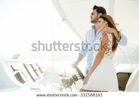 Attractive couple on a yacht enjoy bright sunny day on vacation - stock photo