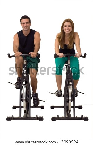 Attractive Couple on exercise bikes smiling. Isolated against a gray studio background. Vertically framed shot - stock photo