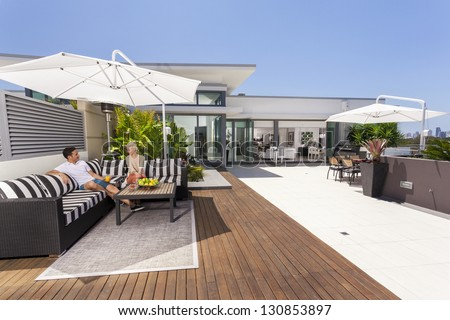 Attractive couple on luxurious penthouse balcony - stock photo