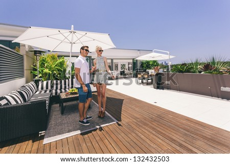 Attractive couple on luxurious penthouse balcony - stock photo