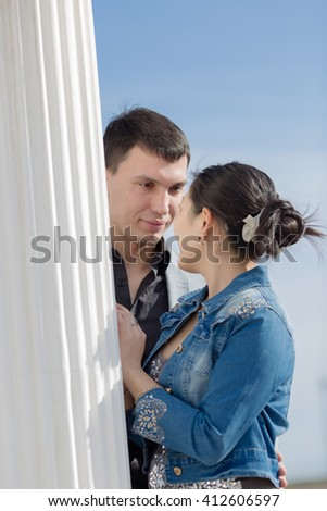 Attractive couple on open air. Asian girl and european guy standing face to face near of column outdoors - stock photo