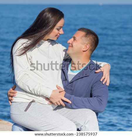 Attractive couple on seashore. Young man and woman sitting on pier looking at each other - stock photo