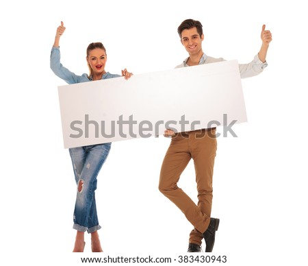 attractive couple posing with legs crossed in isolated studio background while holding white blank sign and showing the victory sign - stock photo