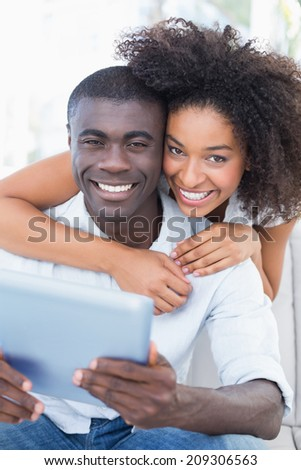 Attractive couple sitting on couch together looking at tablet at home in the living room - stock photo