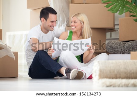 Attractive couple sitting on home floor looking at house plans and smiling at each other. - stock photo
