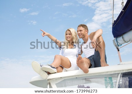 Attractive couple sitting on sailing boat - love. - stock photo