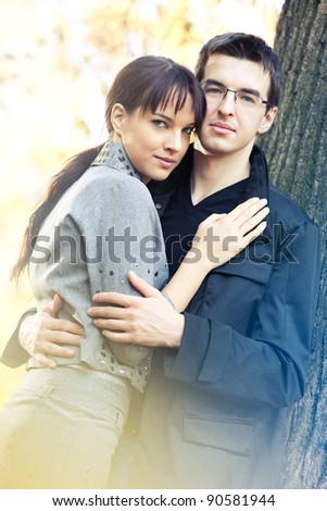 Attractive couple spending sunny day in the autumn park, golden leaves on background - stock photo