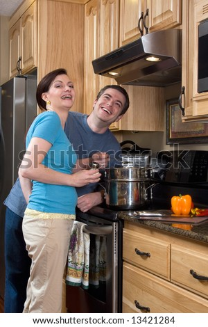 Attractive couple stand in the kitchen by the stove laughing heartily while looking at the camera. Vertically framed shot. - stock photo