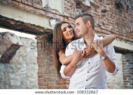 Attractive couple standing against ruined building - stock photo