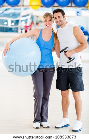 Attractive couple standing at the gym smiling - stock photo
