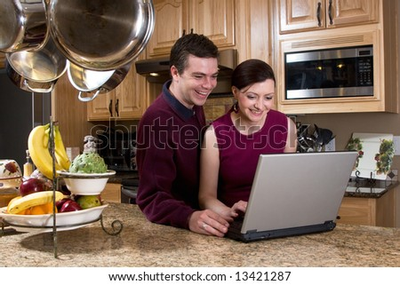 Attractive couple standing in their kitchen and reviewing something on their laptop screen together. Both are laughing and looking at the screen. Horizontally framed shot. - stock photo
