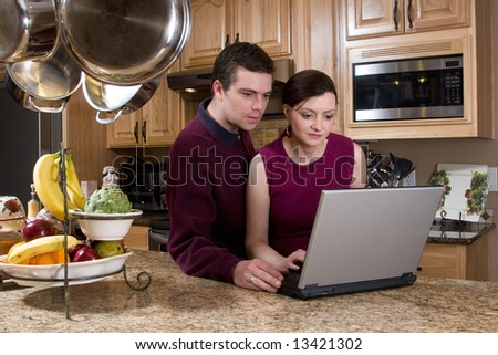 Attractive couple standing in their kitchen and reviewing something on their laptop screen together. Both have serious expressions and are looking at the screen. Horizontally framed shot. - stock photo