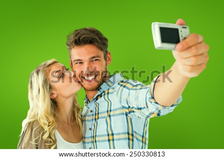 Attractive couple taking a selfie together against green vignette - stock photo