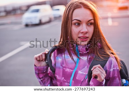 Attractive curious young woman looking aside while adjusting her backpack. A bit tired but still ready to continue her adventure. Freedom, adventures, tourism and backpacking concept. Urban scenery - stock photo