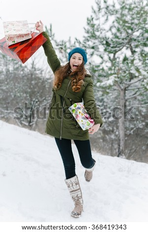 Attractive cute girl in with the shopping bags and gift box in her hands for the valentine's day  - stock photo
