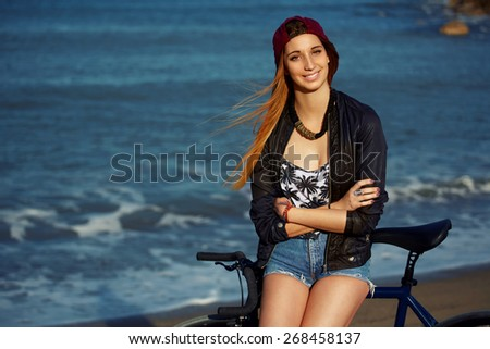 Attractive cute hipster girl leaning on her bicycle while relaxing after ride along seashore, young woman enjoying sunny afternoon during holiday on the beach,female standing with rental bike outdoors - stock photo