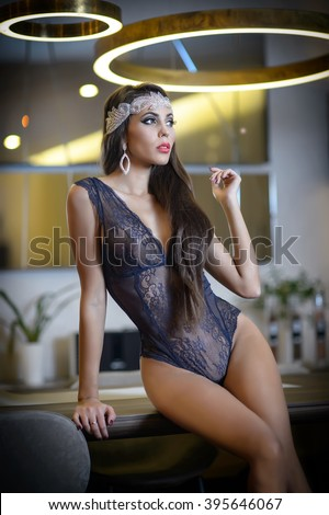 Attractive dark hair model with black lace corset posing provocatively in modern scenery. Fashionable portrait of sensual slim woman with tiara. Beautiful brunette with perfect body, boudoir concept. - stock photo