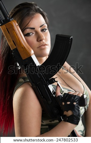 Attractive dark-haired girl in camouflage shirt with a cleavage, held in the hand machine gun, leaning on the shoulder and with a dangerous expression on her face looking at the camera. - stock photo