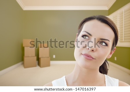 Attractive Daydreaming Young Woman in Empty Green Room with Boxes. - stock photo