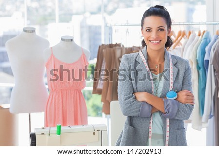 Attractive designer with arms crossed in a studio - stock photo
