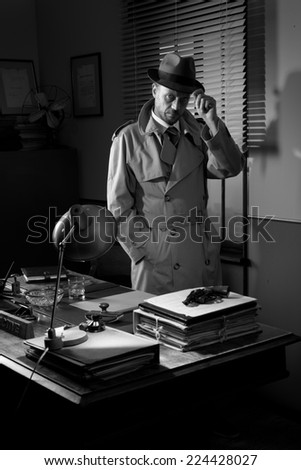 Attractive detective standing next to his desk, 1950s style office. - stock photo